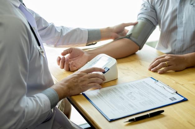 Arts die en bloeddruk van patiënt in het ziekenhuis, gezondheidszorgconcept meten controleren. Premium Foto