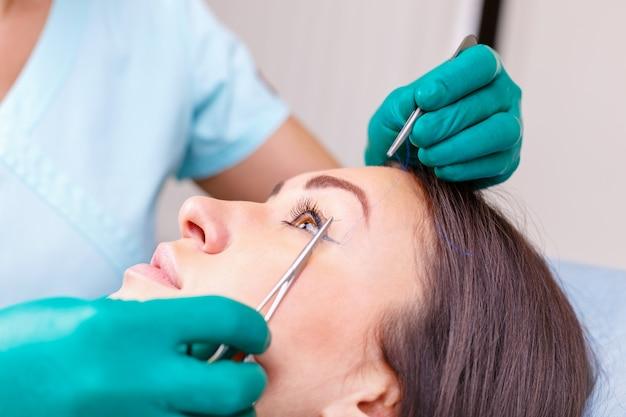 Arts die het gezicht van de vrouw, het ooglid controleert vóór plastische chirurgie, ooglidcorrectie. Premium Foto