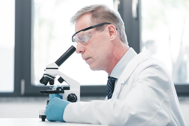 Arts die met een microscoop analyseert Gratis Foto