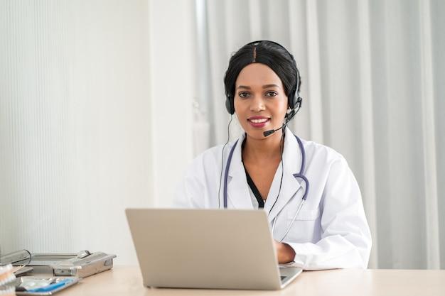 Arts die online aan een patiënt spreekt die aan een pijn lijdt Premium Foto