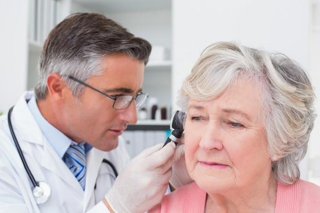 Arts die patiëntenoor met otoscoop onderzoekt Premium Foto