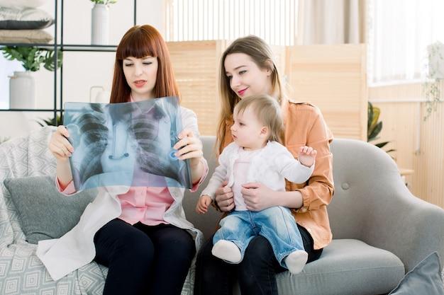 Arts die xray beeld van de borst verklaart aan moeder met weinig dochter, zittend op de grijze bank in de kliniek Premium Foto