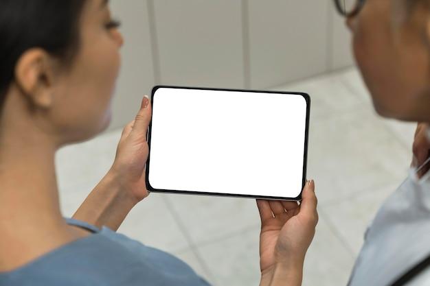 Arts en verpleegster die een lege tablet bekijken Gratis Foto
