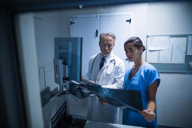 Arts en verpleegster die een röntgenstraal onderzoeken Gratis Foto