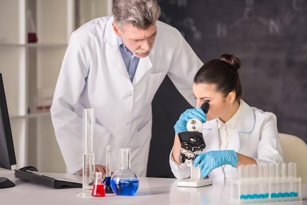 Arts en zijn afgestudeerde student werken aan een stof. Premium Foto