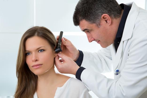 Arts ent oor met otoscoop controleren aan vrouw patiënt Premium Foto