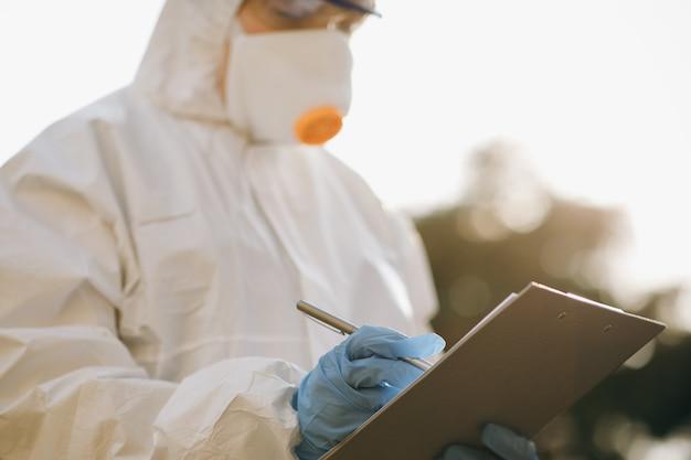 Arts-epidemioloog vecht met coronavirus covid-19. de viroloog hand in een witte handschoen houdt een pen op een blanco vel papier Premium Foto