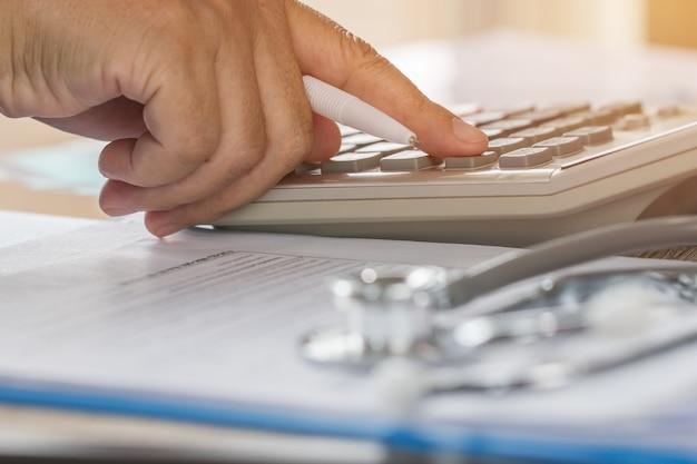 Arts gezondheidszorg wordt berekend op elektronische rekenmachine met stethoscoop Premium Foto