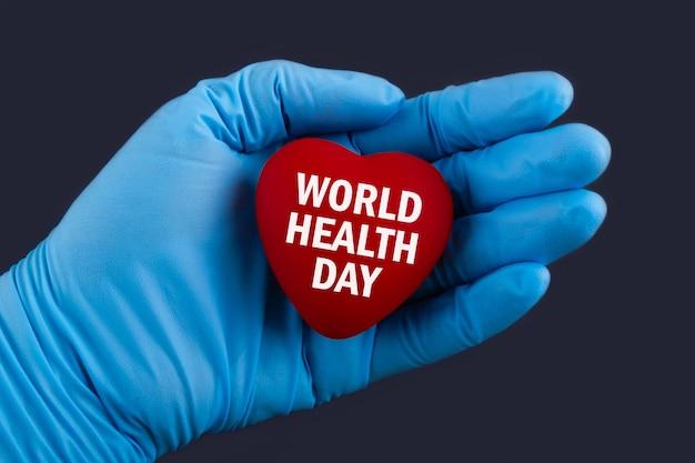 Arts in blauwe handschoenen houdt een hart met tekst wereldgezondheidsdag, concept. Premium Foto