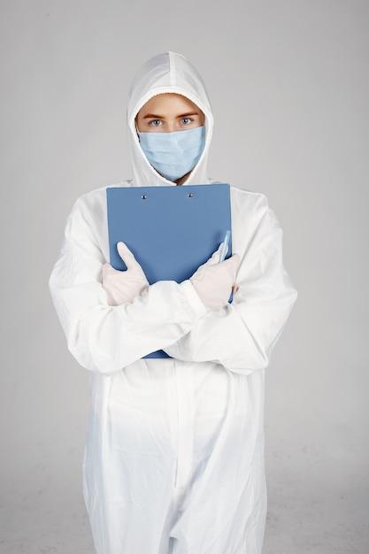 Arts in een medisch masker. coronavirus-thema. geïsoleerd op witte achtergrond. vrouw in een beschermend pak. Gratis Foto