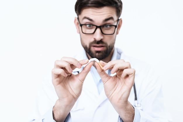 Arts in een witte jas smeert een sigaret. Premium Foto