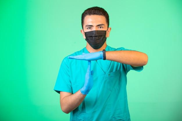 Arts in groen uniform en gezichtsmasker hand gests maken. Gratis Foto