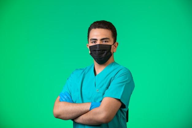 Arts in groen uniform en gezichtsmasker poseren in tevreden positie. Gratis Foto