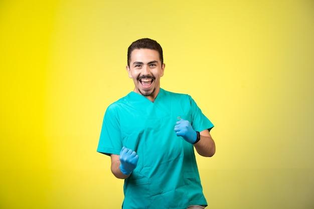 Arts in groen uniform en handmasker dat en zijn geluk glimlacht toont. Gratis Foto
