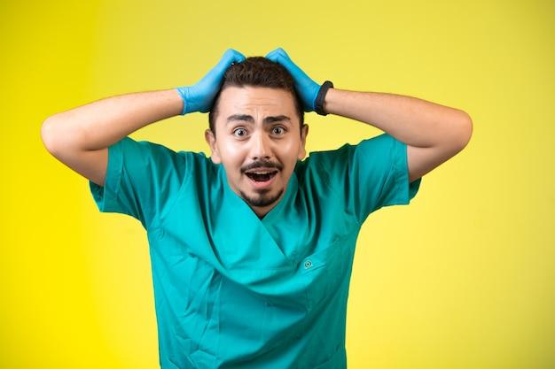 Arts in groen uniform en handmasker dat zijn hoofd omhelst aangezien hij moe is. Gratis Foto