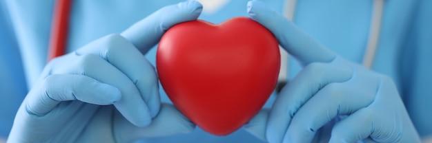 Arts in medische handschoenen houdt speelgoed hart close-up Premium Foto