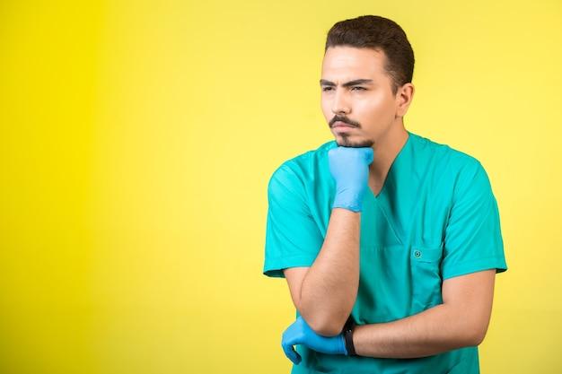 Arts in uniform en handmasker die iets bekijken en overdenken. Gratis Foto