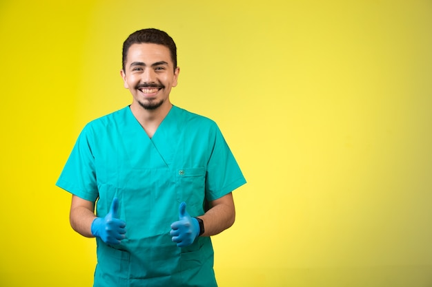 Arts in uniform en handmasker duimen opmaken en glimlachen. Gratis Foto