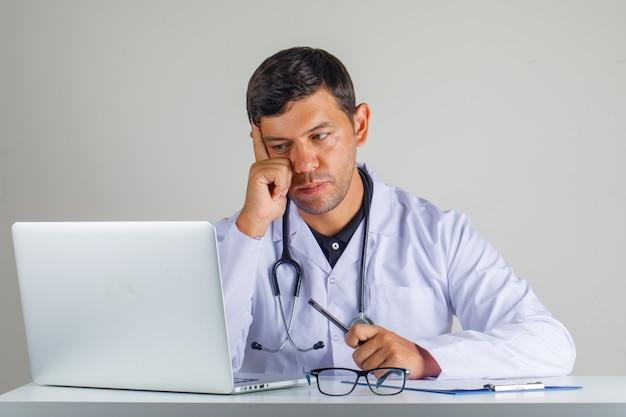 Arts in witte jas, stethoscoop zitten en kijken naar laptop en voorzichtig kijken Gratis Foto