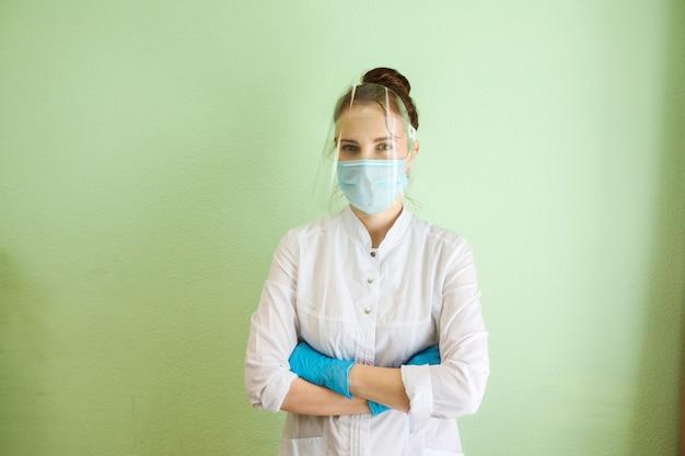 Arts, medisch specialist, schoonheidsspecialiste, tandarts draagt beschermend schild, masker en rubberen handschoenen. medisch uniform. groene muur achtergrond. binnenshuis in kliniek. Premium Foto