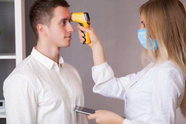 Arts meet de temperatuur van een patiënt tijdens een epidemie covid-19. Premium Foto