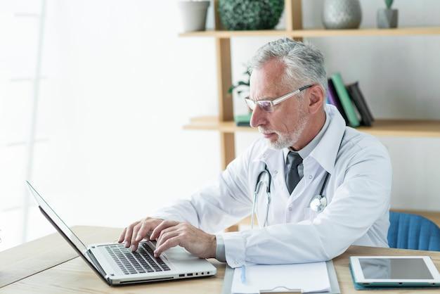 Arts met behulp van laptop op kantoor Gratis Foto