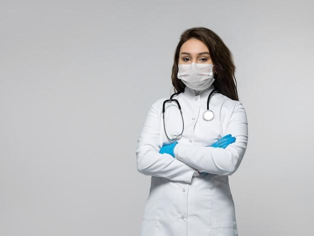 Arts met een stethoscoop in witte medische uniform, gekleed in blauwe handschoenen en witte steriele masker Gratis Foto