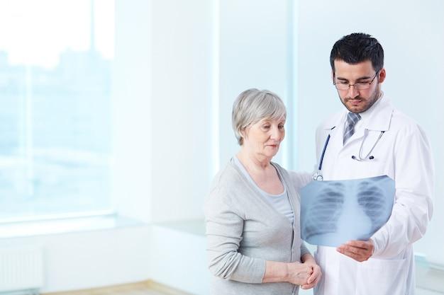 Arts met een x-ray naar oudere patiënt Gratis Foto