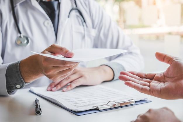 Arts of arts schrijven diagnose en geven van een medisch recept aan mannelijke patiënt Premium Foto