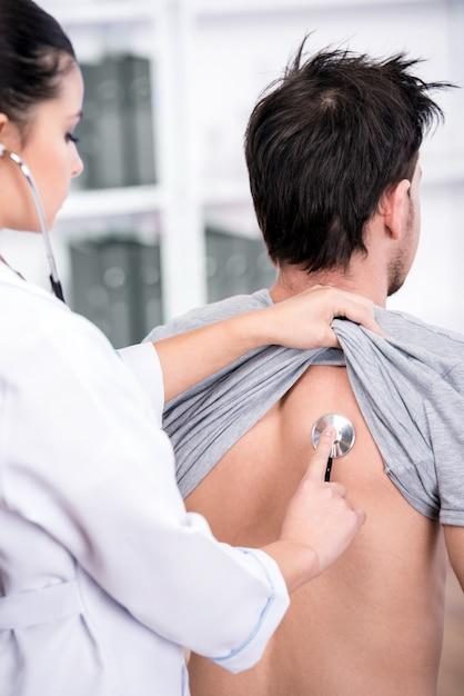 Arts onderzoekt de patiënt longen met een stethoscoop. Premium Foto
