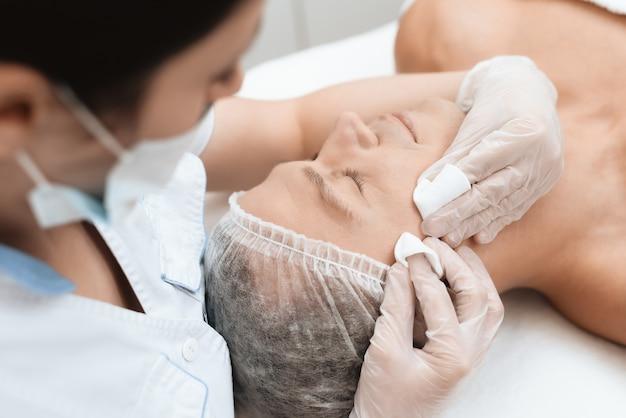 Arts reinigt de huid van de mens. de man ligt op de bank. Premium Foto