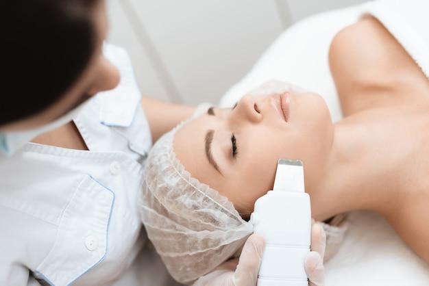 Arts reinigt de huid van de vrouw met een speciaal medisch hulpmiddel. Premium Foto