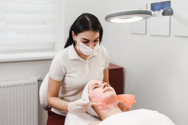 Arts-schoonheidsspecialiste past anti-aging masker toe op het gezicht van de vrouw. girls ligt aan een cosmetologieprocedure Premium Foto