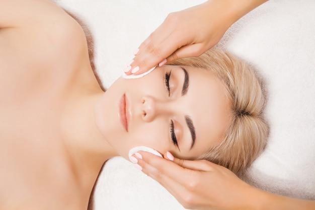 Arts schoonheidsspecialiste reinigt de huid vrouw met een spons in schoonheidssalon. perfecte reiniging - gezichtsverzorging met spa-behandeling. huidverzorging, schoonheid en spa concept Premium Foto