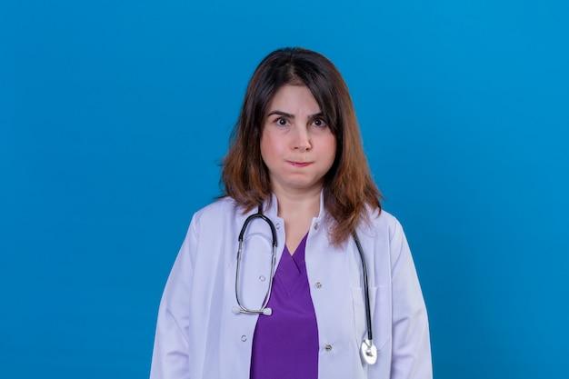 Arts van middelbare leeftijd dragen witte jas en met een stethoscoop ontevreden blazen van wangen over blauwe muur Gratis Foto