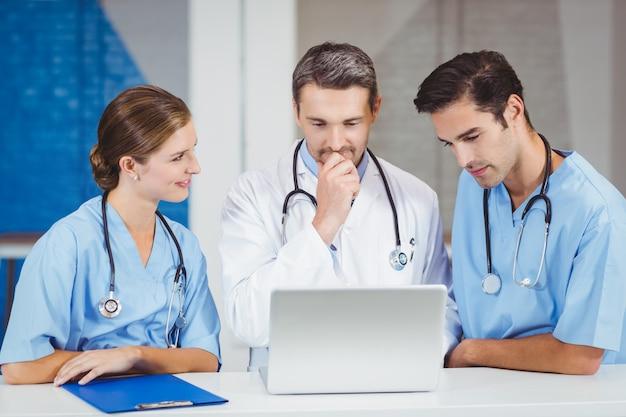 Artsen die laptop met behulp van terwijl status bij bureau Premium Foto