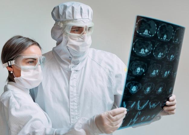 Artsen die op witte achtergrond staan, onderzoeken röntgenfoto voor longontsteking van een covid-19-patiënt in de kliniek. coronavirus concept. Premium Foto