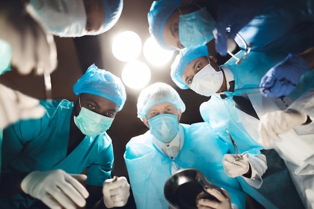 Artsen kijken naar de patiënt, die op de operatietafel ligt Premium Foto