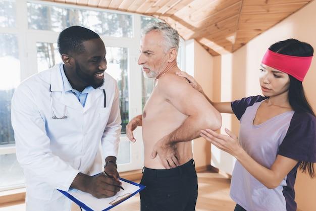 Artsen onderzoeken een oudere man met rugpijn in zijn rug Premium Foto