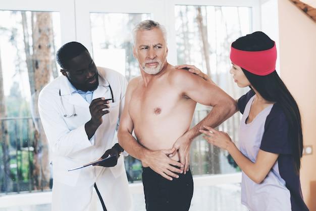 Artsen onderzoeken een oudere man met rugpijn. Premium Foto