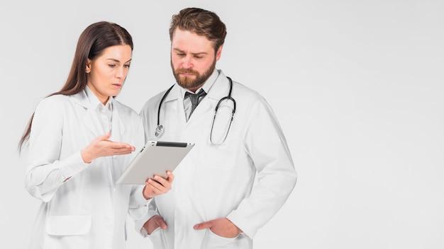 Artsenvrouw en man die tablet bekijken Gratis Foto