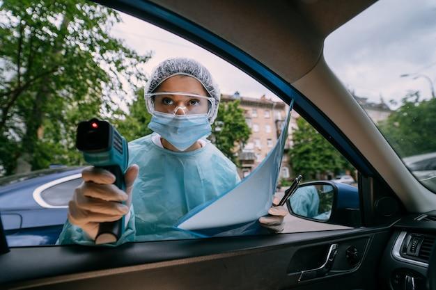 Artsenvrouw gebruikt infrarood voorhoofdthermometer om de lichaamstemperatuur te controleren. voor virus covid-19 symptomen. vrouw met de isolatie jurk of beschermende pakken en chirurgische gezichtsmaskers buiten. Gratis Foto