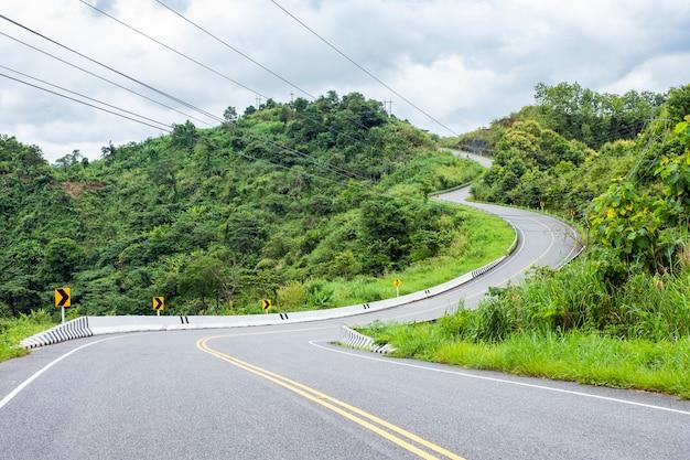 Asfaltweg op heuvel wordt gebogen die Premium Foto