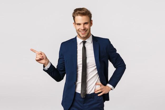 Assertieve charismatische blonde zakenman met varkenshaar, draag klassiek pak, naar links wijzend en glimlachend, vertellend over geweldig product, adverteer financiële app, bedrijfsconcept Premium Foto