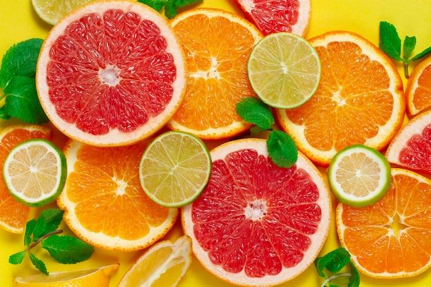 Assortiment citrusvruchten, op een gele achtergrond, bovenaanzicht, geen mensen, horizontaal, Premium Foto
