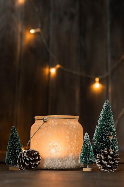 Assortiment met kerstbomen en kaars Gratis Foto