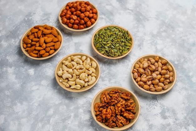 Assortiment noten in keramische platen. cashewnoten, hazelnoten, walnoten, pistache, pecannoten, pijnboompitten, pinda, rozijnen. bovenaanzicht Gratis Foto