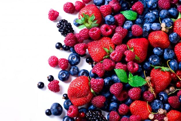 Assortiment van aardbei, bosbes, bes, muntblaadjes. voedselkader, grensontwerp. veganistisch en vegetarisch concept. Premium Foto