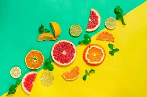 Assortiment van citrusvruchten, op een geelgroene achtergrond, geen mensen, horizontaal Premium Foto