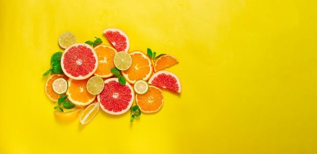 Assortiment van citrusvruchten, op een gele achtergrond, geen mensen, horizontaal Premium Foto